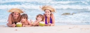 Happy family lying on the beach and drinking coconut drink